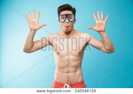 Portrait of a cheerful young shirtless man in swim mask having fun over blue background