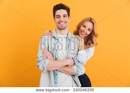 Portrait of loving couple man and woman in basic clothing looking at camera with happy smile isolated over yellow background