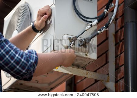 Closeup Photo Of Male Engineer Connecting Pipes To Outdoor Air Conditioner System