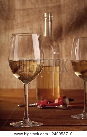 One Glass Bottle And Two Bocals With White Wine Standing On Brown Wooden Table Top Near Red Plastic