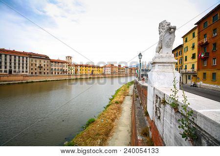 Old residential architecture with river Arno and monument on the river embankment in Pisa, Italy. poster