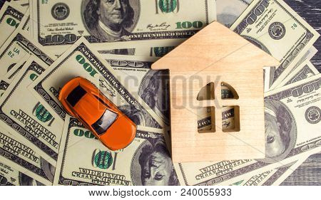 A Wooden House Model And Car With American Dollars. Buying And Selling Or Car Insurance. Concept Of