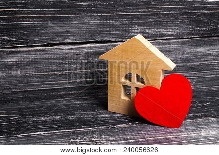 Wooden House With A Red Heart On A Dark Wooden Background. A House For Lovers, A Honeymoon. Purchase