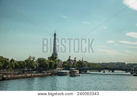 Paris, France - July 07, 2017. Seine River Bank With Boats, Trees, Bridge And The Eiffel Tower At Su