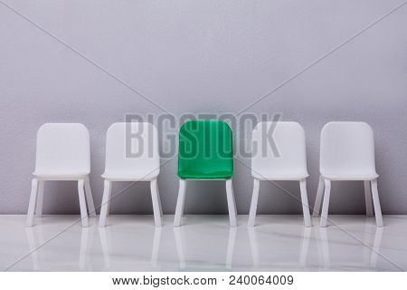 Miniature Chair In A Row With A Green One In The Middle On Grey Background