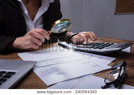 Businessperson Analyzing Invoice In Office