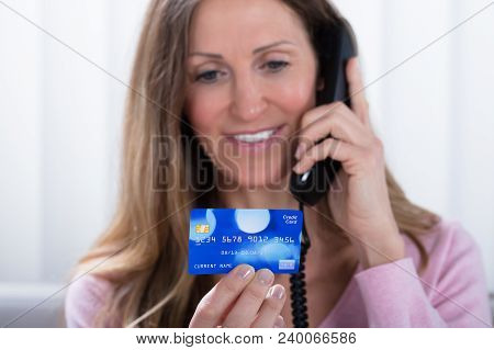 Close-up Of Mature Woman Holding Credit Card While Talking On Telephone At Home