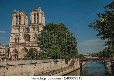 Paris, France - July 08, 2017. People, Tree-lined Seine River And Gothic Notre-dame Cathedral At Par