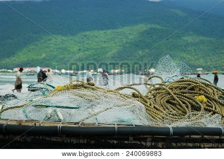 Fishing Nets And Rope Rest On Top Of A Traditional Vietnamese Fishing Boat. In The Background, Men S