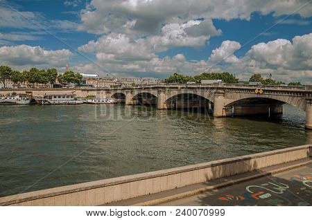 Paris, France - July 11, 2017. Boats Anchored At The Seine River Bank With Trees And Bridge Under A