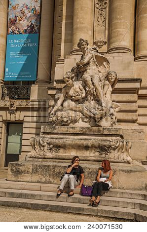 Paris, France - July 11, 2017. People Sit On Steps Under Statue At The Petit Palais In Paris. Known