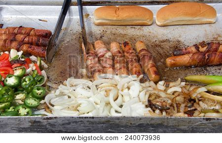 Hot Dog Street Vendor Grill With Bacon Wrapped Hot Dogs, Onions, Peppers, Jalapenos On A Steaming Gr