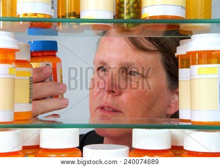 Middle Aged Caucasian Woman Reading Medication Label On Prescription Bottle In Medicine Cabinet, Vie
