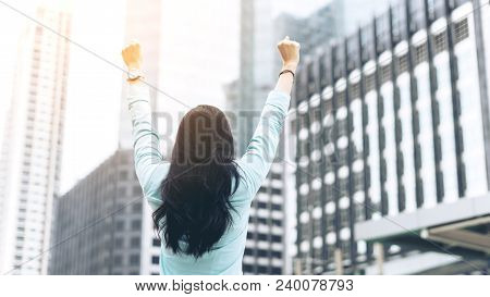 Successful Business Woman Celebrating With Arms Up On Business District , Business Concept