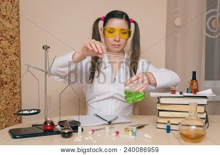 Emotional Student Girl On Chemistry Lesson Demonstrates Fluid In Vitro. Pharmacist Or Apothecary Wom