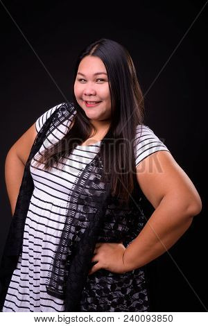 Studio Shot Of Beautiful Overweight Asian Woman Against Black Background
