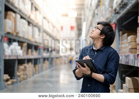 Young Asian Man Doing Stocktaking Of Product In Cardboard Box On Shelves In Warehouse By Using Digit