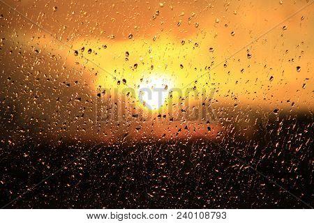 Rain Outside Window On Background Of Sunset. Rain Drops On Glass During Rain. Sunset Outside Window