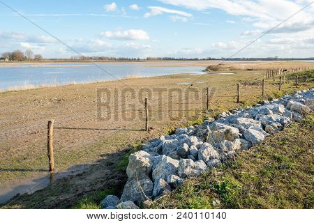 Flooded Part Of A Dutch Polder With In Front A Fence Of Wooden Poles And Wire As Well As Rock Chunks