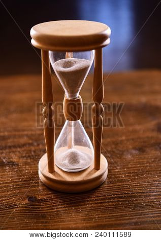 Hourglass On Wooden Table, Dark Background. Sand Falling Down Inside Of Hourglass. Time Flow Concept