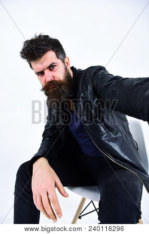 Man With Beard And Mustache On Strict Face Looks At Camera. Macho Wears Leather Jacket, White Backgr