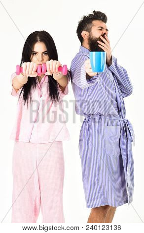 Couple, family offers alternative energy source. Couple in love in pajama, bathrobe stand isolated on white background. Girl with dumbbell, man with coffee cup. Alternative lifestyle concept. poster