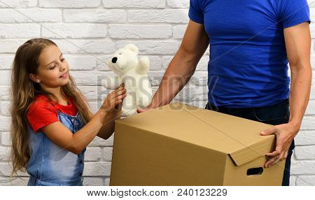 Dad And Daughter Hold Cardboard Box. Moving In Or Out Concept. Girl Plays With White Teddy Bear On W