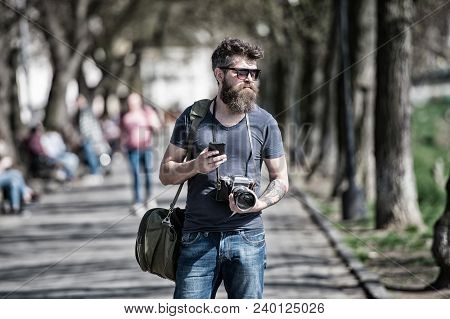 Bearded Man Carries Bag On Shoulder And Holds Camera. Photographer Concept. Man With Long Stylish Be