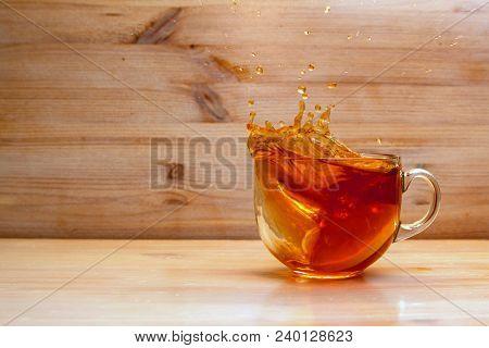 Close Up Transparent Teacup With Black Tea Spilling Over Because Of Added Lemon