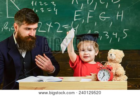 Little Boy Shows His Copybook With Paintings. Kid Happy Studies Individually With Father, At Home. I