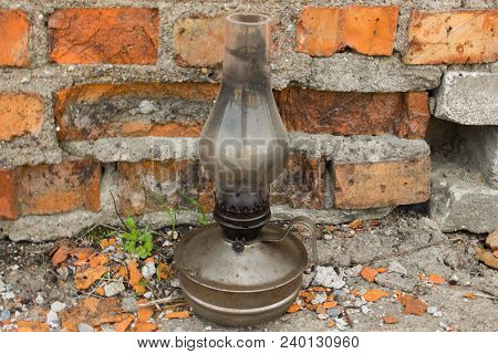 An Old Kerosene Lamp. Old Lamp. Kerosene Lamp. Kerosene Lamp On A Background Of Red Bricks.