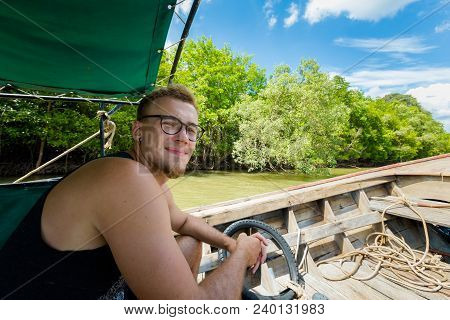 Man Travelling On Longtail Boat On Pak Nam River In Krabi In Southern Thailand. Landscape Taken From