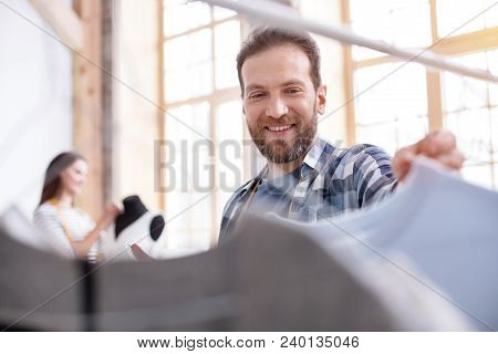 What About This. Low Angle Of Vigorous Male Stylist Choosing Garment While Grinning