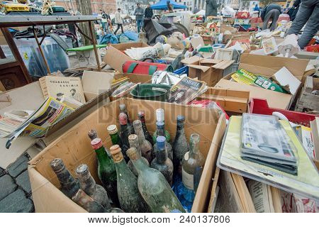 Brussels, Belgium - Apr 3: Flea Market With Old Wine Bottles, Bargains And Antique Stuff In Boxes Of