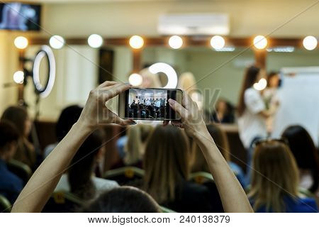 Hands Of A Girl With A Phone On The Blurred Background Of A Master Class.the Girl Remove On The Phon