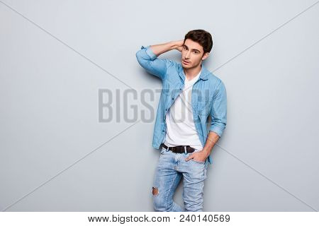 Portrait Of Stylish, Stunning, Virile Man In Denim Outfit Holding Hands In Pocket And Behind The Hea