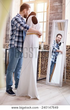 Dream Dress. Low Angle Of Proud Male Couturier Measuring Dress While Looking At Mirror