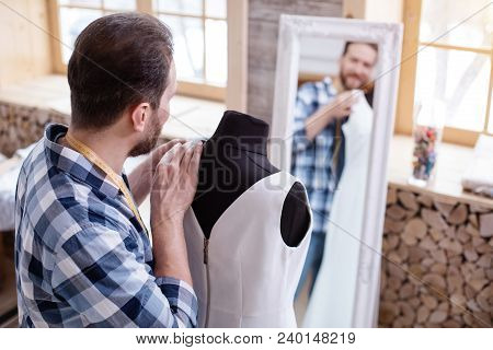 Wedding Style. Ambitious Male Couturier Modifying Dress While Looking At Mirror
