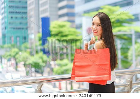 Smiling Attractive Young Women Hold Shopping Bags At Street Centre. Beautiful Young Mixed Race Cauca