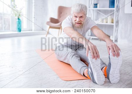 Supple Body. Upbeat Senior Man Bending Forward And Touching His Toes While Sitting On The Yoga Mat A