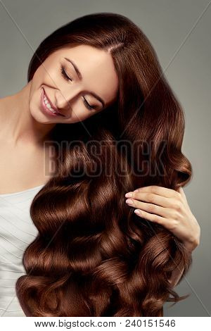 Hair. Beautiful Girl With Long Wavy And Shiny Hair. Brunette Woman With Gorgeous Curly Hairstyle. Ha