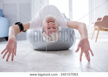 Enjoying Himself. Upbeat Elderly Man Lying On His Back On The Fitness Ball And Waving At The Camera