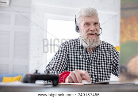 Avid Player. Upbeat Senior Man Sitting At The Table And Playing A Video Game Online With His Friends