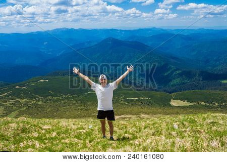 Summer Hiking In Mountains. Young Tourist Man In Cap With Hands Up On Top Of Mountains Admires Natur