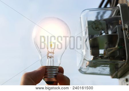 Hand Of Person Holding Light Bulb From Outdoor With Watt Hour Meter Beside.