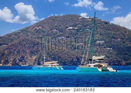 Luxury sailing catamarans near a resort island in BVI