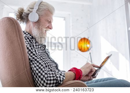 Enjoying Free Time. Upbeat Senior Man Sitting In The Armchair And Playing On The Tablet While Smilin