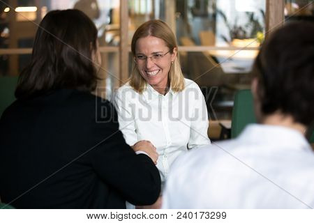 Smiling Businesswoman Shaking Hand Of Businessman At Group Negotiations Or Job Interview, Friendly W