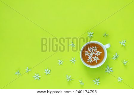 Cup Of Tea With White Flowers On Bright Green Surface, Top View. Many Blossom Flower Heads Ornithoga