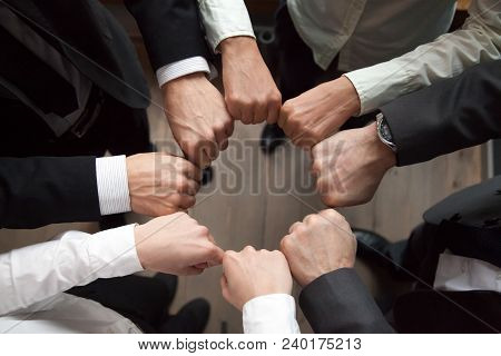 Business Team Or Partners Put Fists In Circle As Concept Of Motivating Engaging Teambuilding Activit